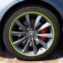 Close Up View Of Grey Tesla Model S Silver Alloy Wheel With Green AlloyGator Wheel Protector & Red Callipers