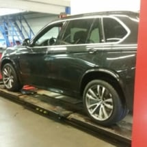 Side View Of Black BMW With Silver Alloy Wheels And Black AlloyGator Wheel Protectors On A Garage Maintenance Ramp
