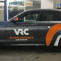 Side View Of A Grey BMW With A RIJOPLEIDINGEN Orange / White Branding, Silver Alloy Wheels & Orange AlloyGator Wheel Protection With Match The Orange Brand Colour.