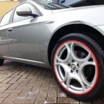Side View Of An Alfa Romeo With Silver Alloy Wheels And Red AlloyGator Rim Protectors