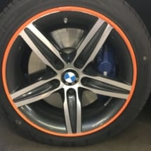 Close Up View Of A Single Silver BWM Alloy Wheel With A Orange AlloyGator Wheel Protector