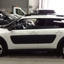 White Citroen with silver dimond cut alloy wheels and white AlloyGator wheel protection in a garage