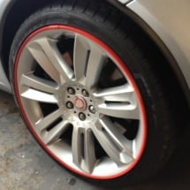 Close Up Of A Silver Jaguar Alloy Wheel With Red AlloyGator Alloy Wheel Protector