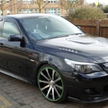 Side View Of Modified Black BMW With Custom Silver Alloy Wheels And Green AlloyGator Wheel Rim Protectors