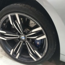 Close Up Of A BMW Dimond Cut Black And Silver Alloy Wheels, Black AlloyGator Wheel Protector And Blue Break Callipers