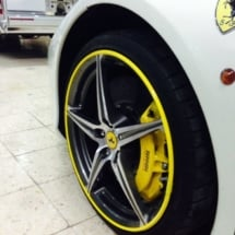 Side View Of A White Ferrari Front Alloy Wheel With Yellow AlloyGator Alloy Wheel Protector And Yellow Brake Callipers
